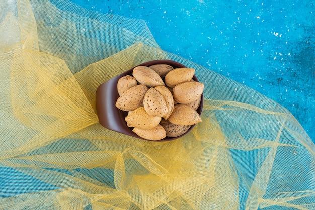 Una ciotola di mandorle sgusciate su tulle, sul tavolo blu.