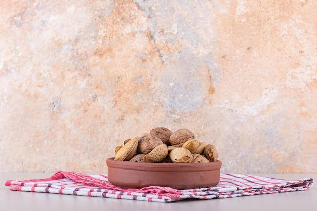 Ciotola di mandorle e noci organiche sgusciate su fondo bianco. foto di alta qualità