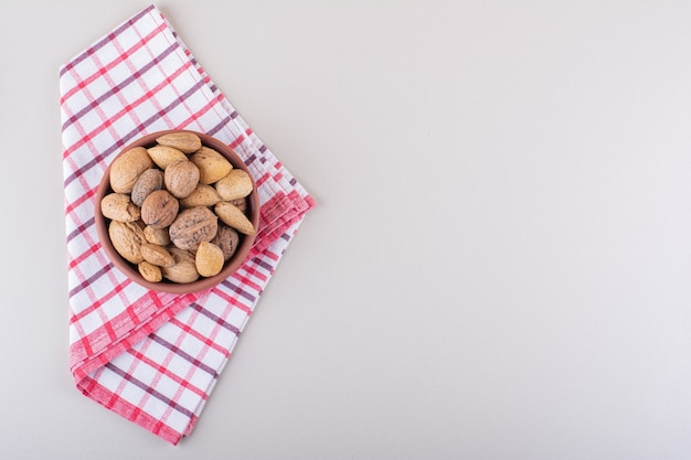 Bowl of shelled organic almonds and walnuts on white background. high quality photo