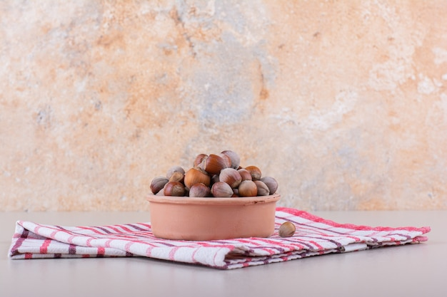 Bowl of shelled organic hazelnuts placed on white background. high quality photo