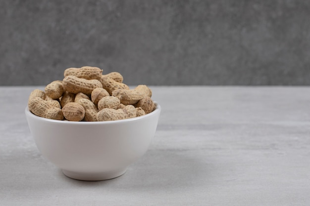 Bowl of shelled peanuts on marble background.