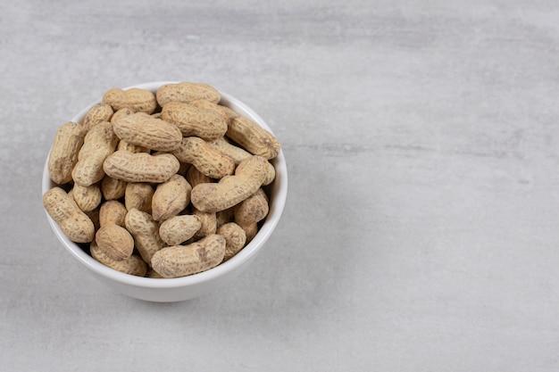 Ciotola di arachidi sgusciate su fondo marmo.