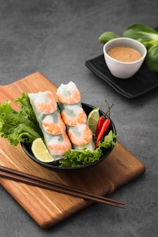 Bowl of shrimp rolls on chopping board with salad