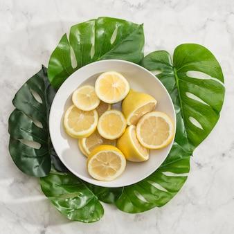 Ciotola di limoni a fette con foglie di monstera