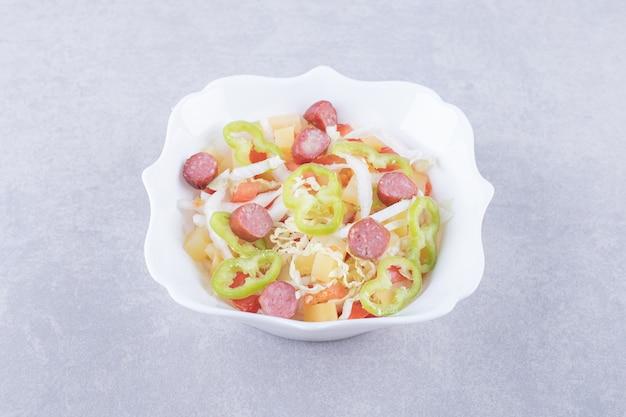 Ciotola di salsicce affumicate e verdure tritate su fondo di pietra.