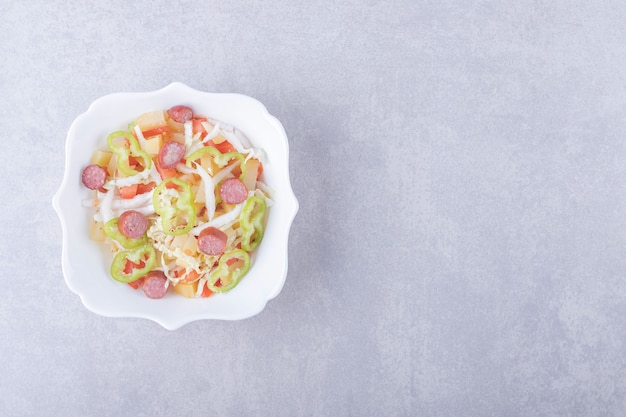 Bowl of smoked sausages and chopped vegetables on stone background.