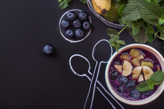 Bowl of smoothies with berries on a chalkboard with spoons