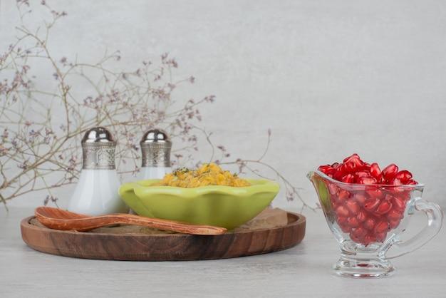 Ciotola di minestra, sale e semi di melograno sulla superficie bianca.
