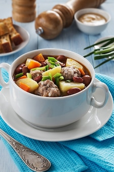 Bowl of soup with beans and meatballs