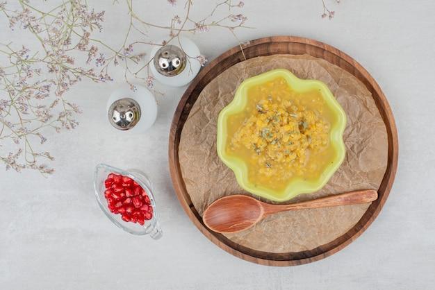 Ciotola di zuppa sul piatto di legno con semi di melograno e sale.
