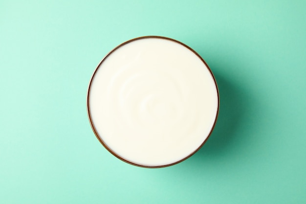 Bowl of sour cream on mint background, top view