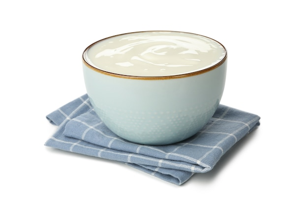 Bowl of sour cream yogurt and napkin isolated on white