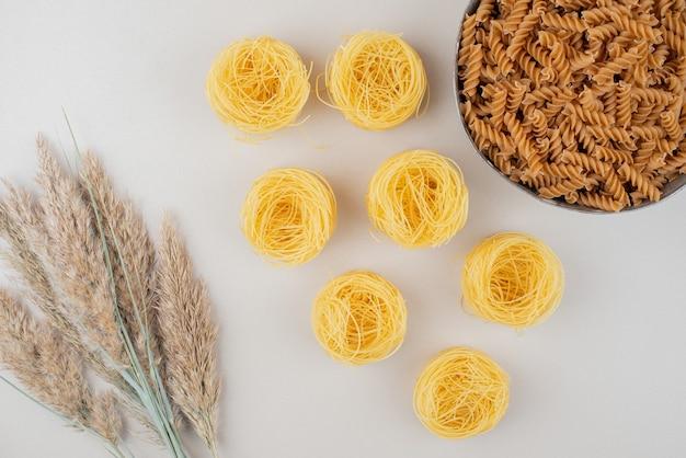 Ciotola di pasta a spirale e nidi di spaghetti sulla superficie bianca