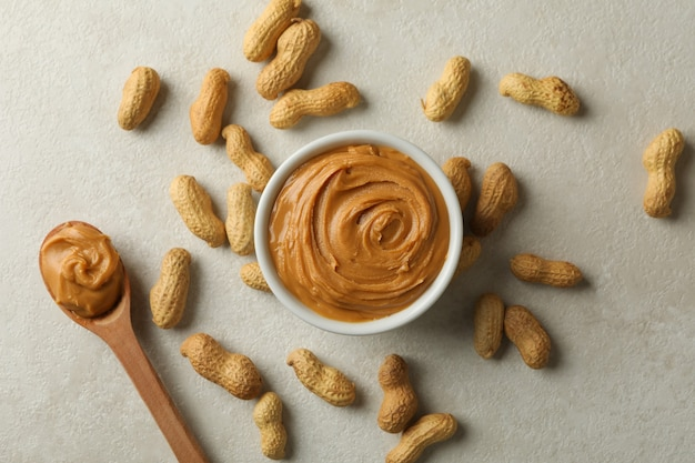 Bowl and spoon with peanut butter, and peanut on gray background