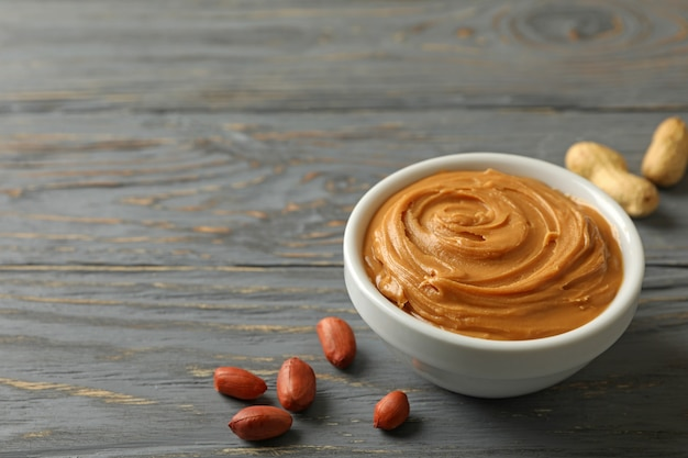 Bowl and spoon with peanut butter on wooden background