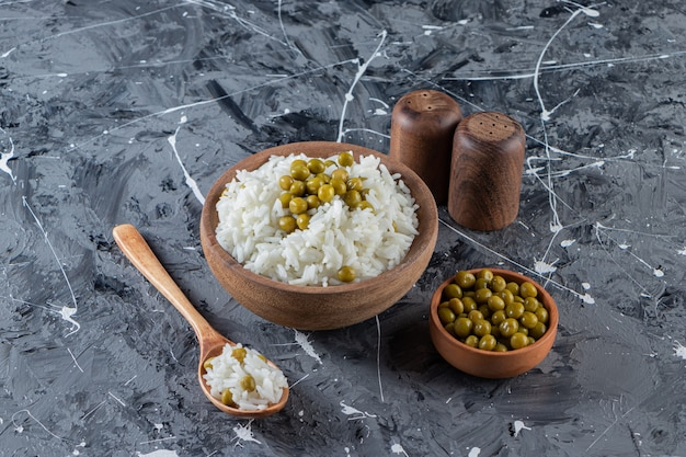 Bowl of steamed white rice with green peas on marble background.