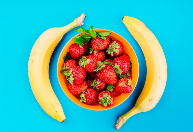 Bowl of strawberries between the bananas against blue background
