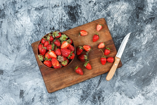 A bowl of strawberries and a knife on a wooden cutting board on a dark blue marble background. flat lay.