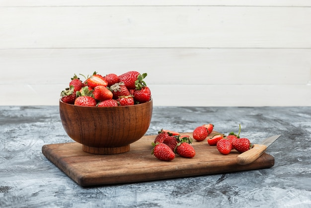 A bowl of strawberries and a knife on a wooden cutting board on a dark blue marble and white wooden board background. close-up. free space for your text