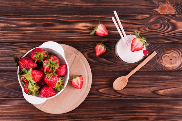 Bowl of strawberries and milkshake on table