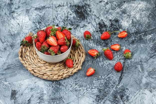 A bowl of strawberries on a round wicker placemat on a dark blue marble background. .