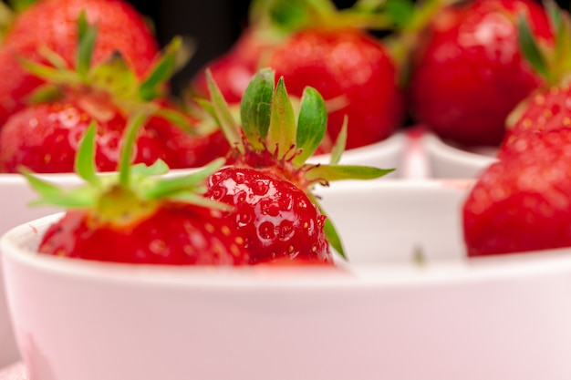 Bowl of strawberry harvest on wooden table close up