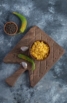 Bowl of sweet corn, garlic and pepper on wooden board.