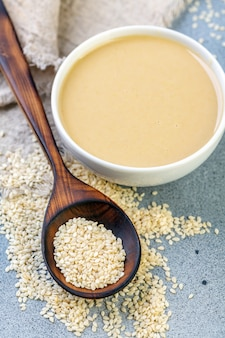Bowl of tahini and spoon with white sesame seeds