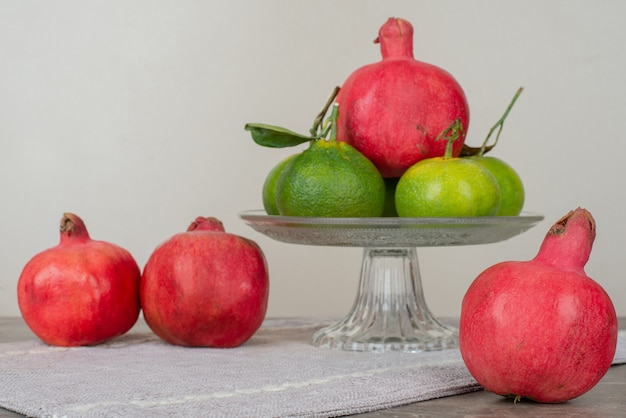 Bowl of tangerine and pomegranates on gray tablecloth.