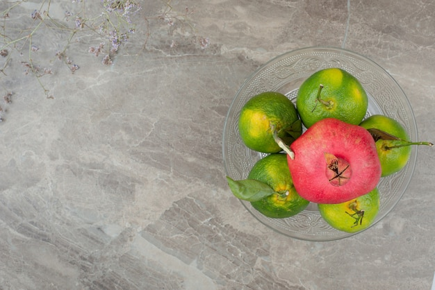 Bowl of tangerine and pomegranates on marble.