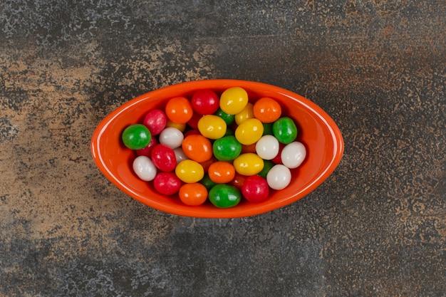 Ciotola di gustose caramelle su marmo.