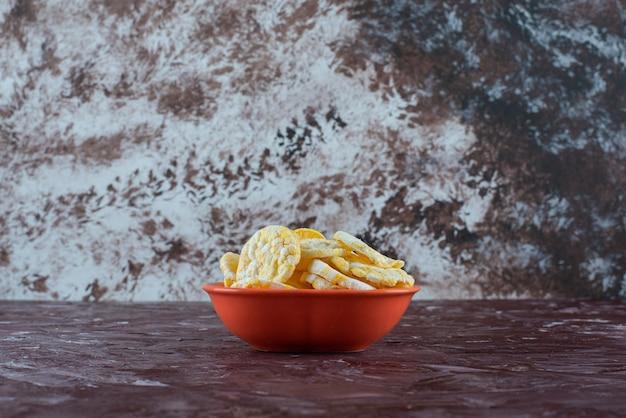 Una ciotola di gustose patatine al formaggio su marmo.