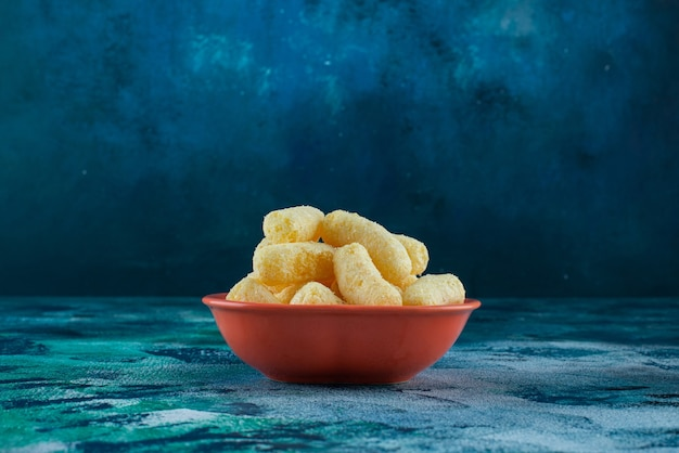 A bowl of tasty corn sticks on blue.