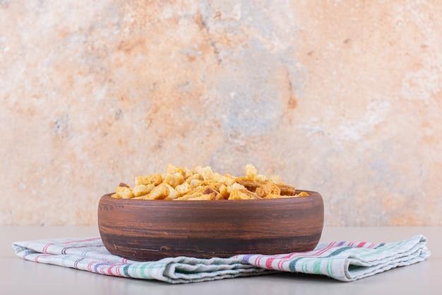 Ciotola di gustosi cracker croccanti con tovaglia su sfondo marmo.