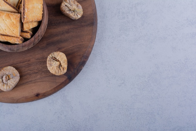 Bowl of tasty crunchy crackers and dried figs on wooden board.
