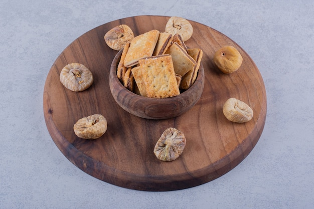 Ciotola di gustosi cracker croccanti e fichi secchi su tavola di legno.