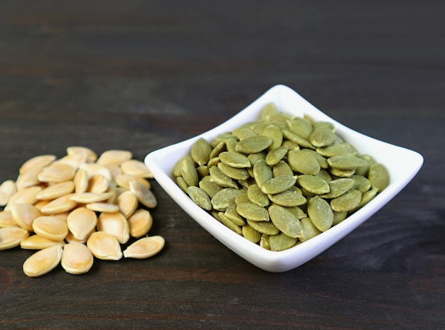 Bowl of tasty and healthy roasted pumpkin seeds with heap of raw seeds on wooden table