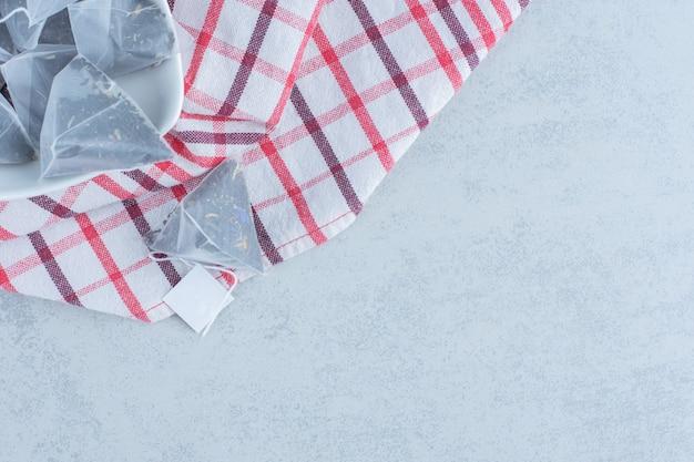 Una ciotola di bustine di tè su un asciugamano su marmo.