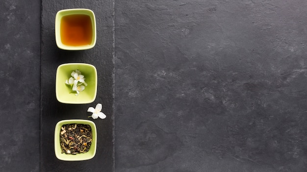Bowl of tea and it's ingredient arrange in a row on slate stone over black surface