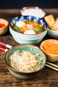 Bowl of thai beans sprout and fish ball soup on wooden desk