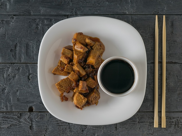 A bowl of tofu and soy sauce on a wooden table