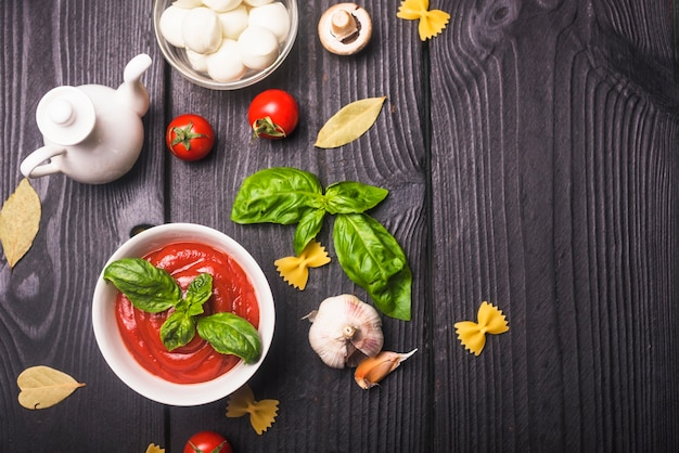 Bowl of tomato sauce with ingredients on table