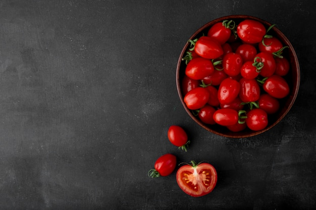 Bowl of tomatoes on right side on black surface