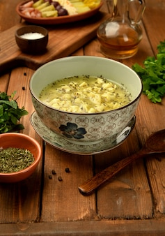 Bowl of traditional azerbaijani dushbara dumpling soup served with vinegar and dried mint