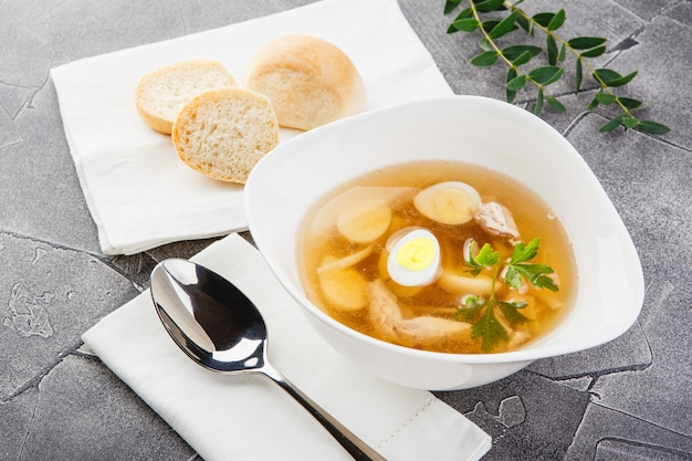 Bowl of traditional chicken stock with homemade noodles, boiled quail egg and parsley garnished on gray background