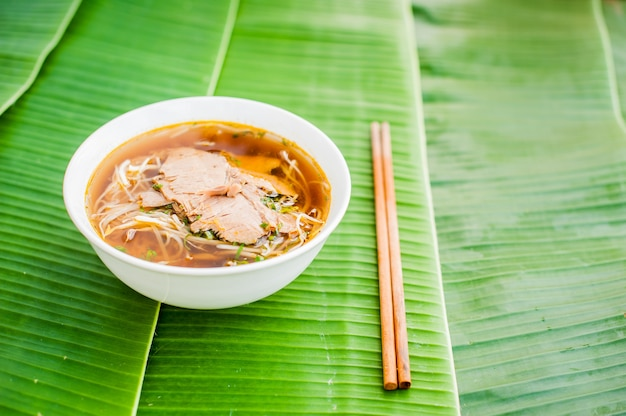 Bowl of traditional vietnamese beef soup pho bo on banana leaf background.
