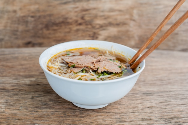 Bowl of traditional vietnamese beef soup pho bo at the dark old wooden background
