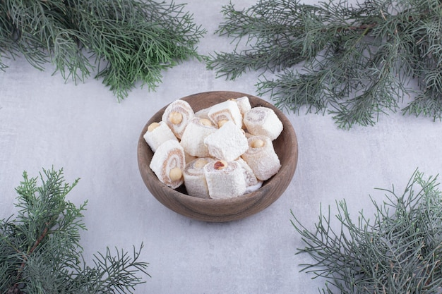 Bowl of turkish delight and pine branches on white surface