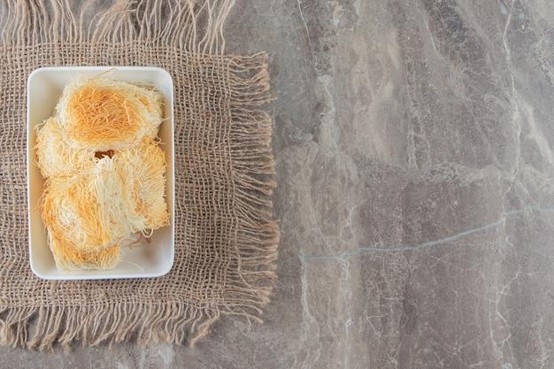 Una ciotola di kadayif turco del dessert su una struttura sul blu.