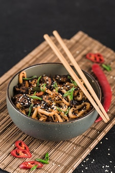 A bowl of udon noodles with squid rings and mushrooms with chopsticks and chili pepper on a dark surface